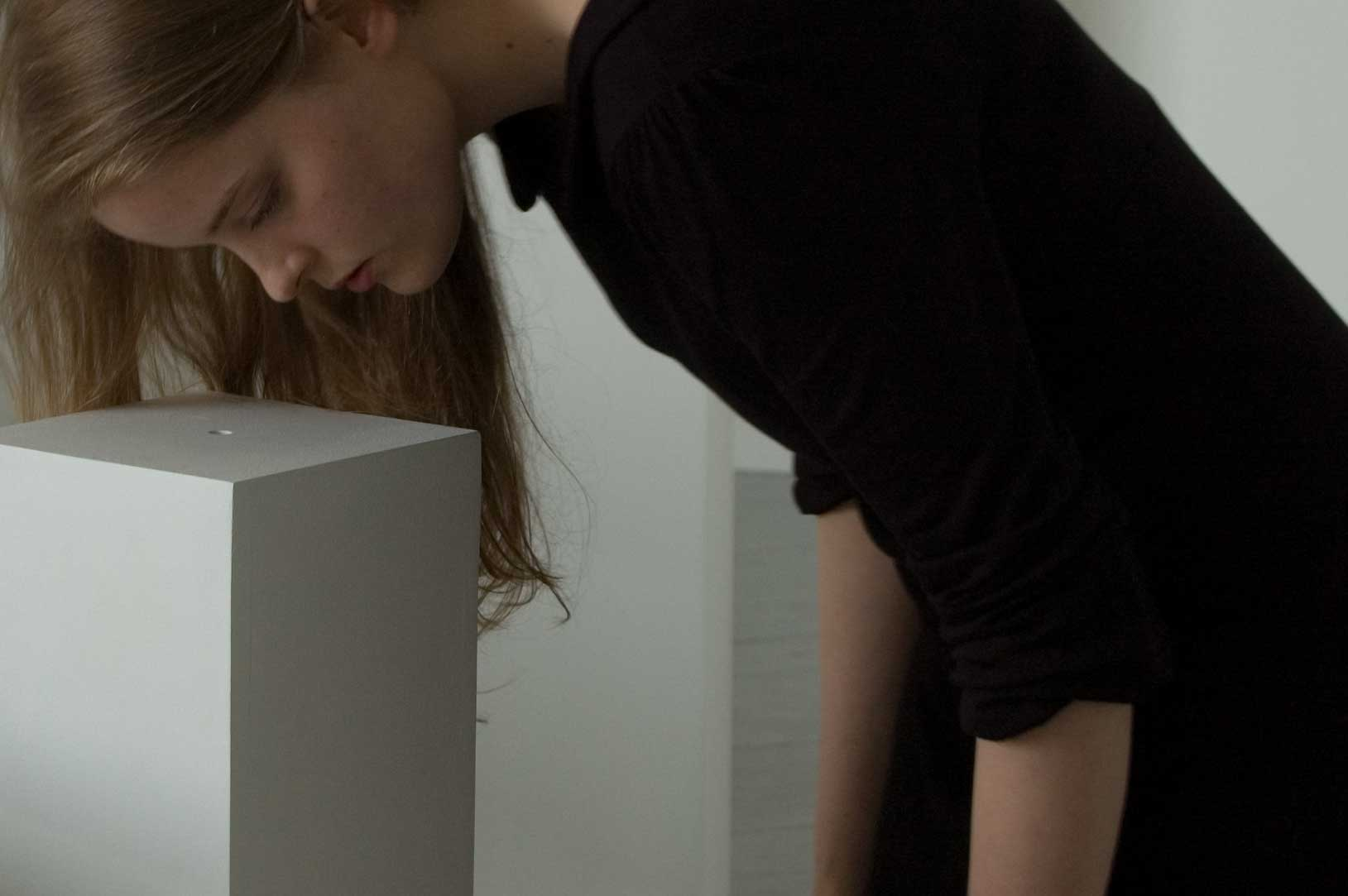 A woman leans over a plinth looking into a small hole in the top of the plinth.