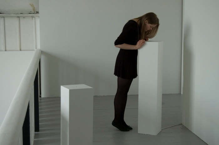 A white walled gallery space with grey floors and two white plinths can be seen. One of the plinths is taller than usual. A woman, dressed in black, is leaning up and looking into this plinth. A cable can be seen running into the bottom of the plinth.