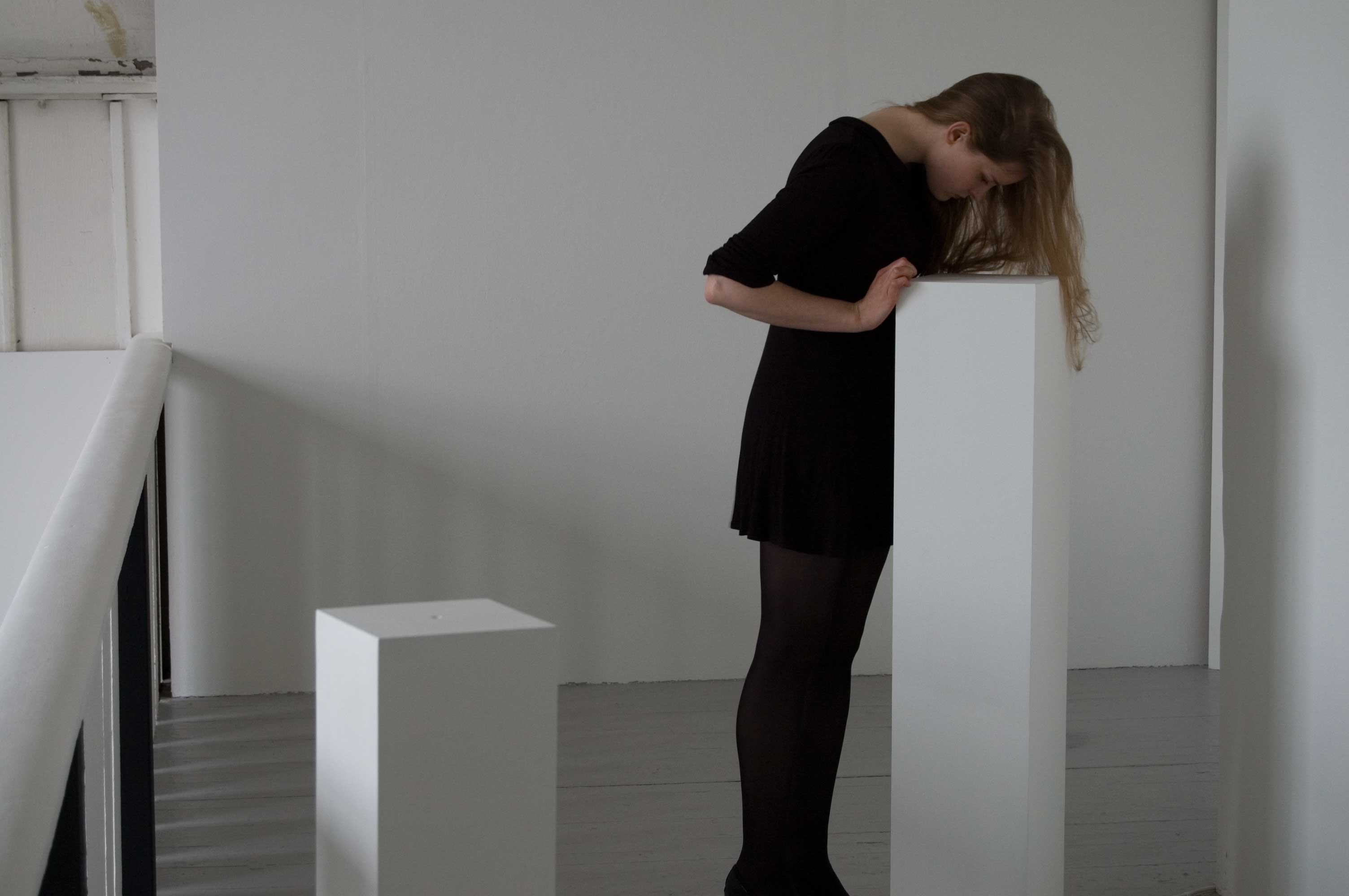 A gallery space with white walls. There are two plinths, a woman leans over one of the plinths to look into a hole in the top of it.