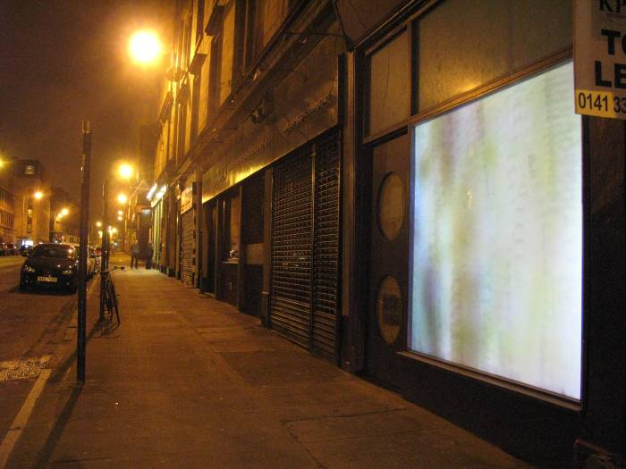 Nighttime. A city street with closed shops. One shop window has been turned into a projection screen. An abstract, pixelated image can be seen on the screen.