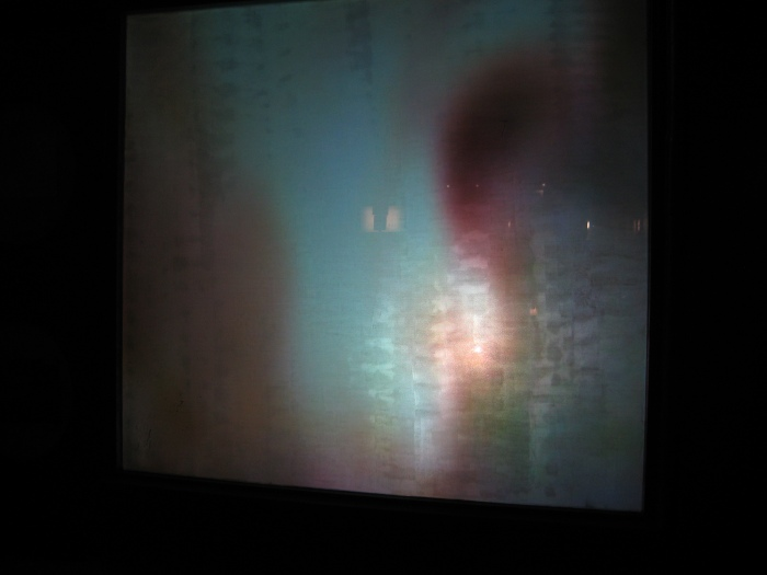 a very abstract/pixelated image of the projection in the shop window shows a close up of a woman with her mouth open to yawn