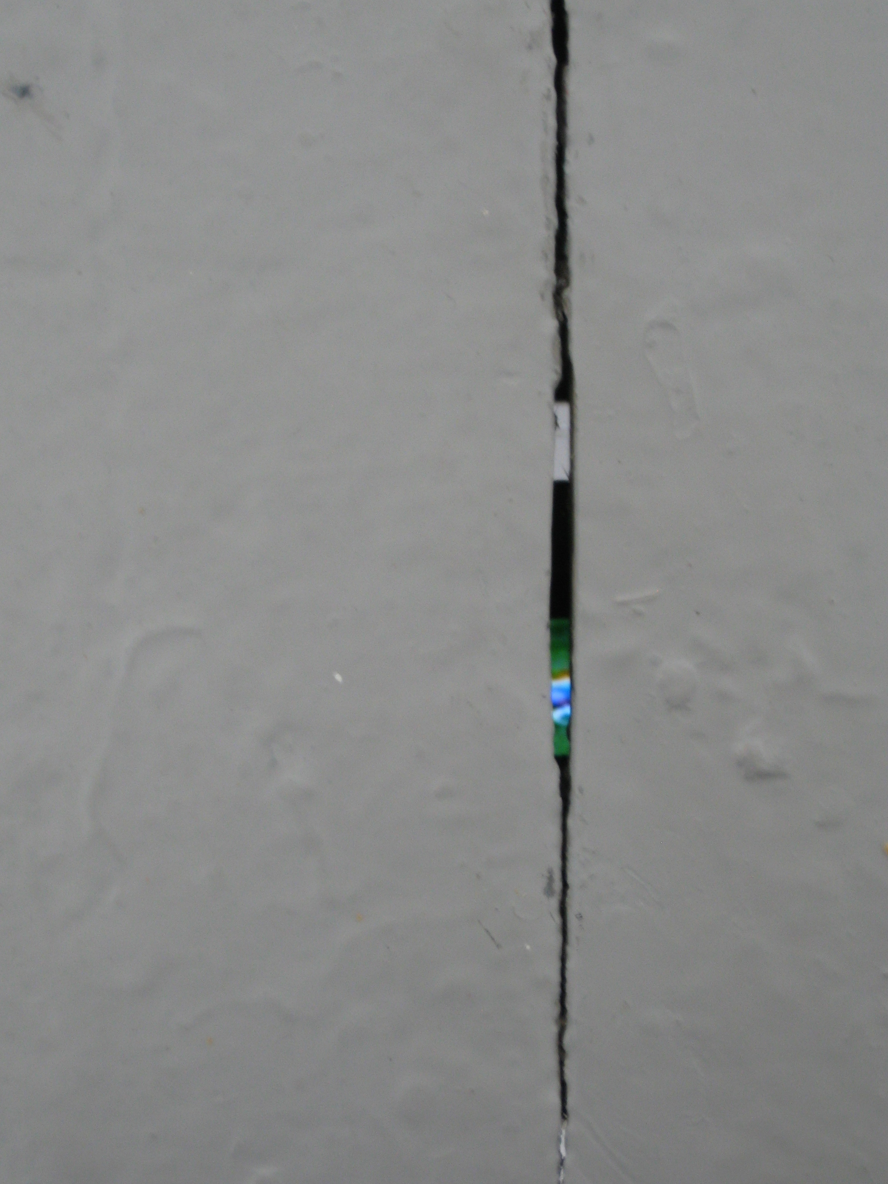 grey painted floorboards with a small gap between them, the colourful pixels of a mobile phone can be glimpsed.