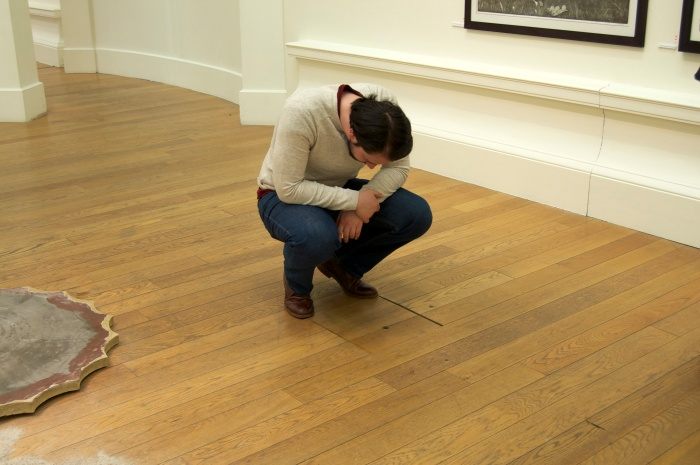 A gallery space with wooden floors. A man crouches down to look into a small hole in the floor.