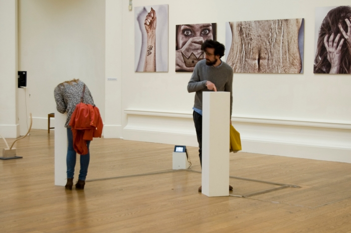 A gallery space. Two white plinths are on the floor, a couple of metres apart. On the left, a woman is leaning over and looking into the smaller of the two plinths. On the right, a man in pointing into the taller plinth.