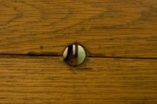 Close up. Wooden floor with a small hole in it. Through the hole a little screen can be seen, the video shows peoples' legs.