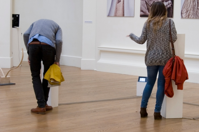 Two white plinths are in a gallery space. They have peepholes in the top and two viewers look into the plinths and gesture to each other.