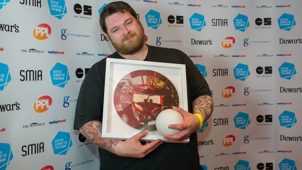 RM Hubbert, winner of SAY Award 2013, with the two awards 'hold' a herculite sphere by Emma Helen Reid and a framed award by Gregor Morrison.
