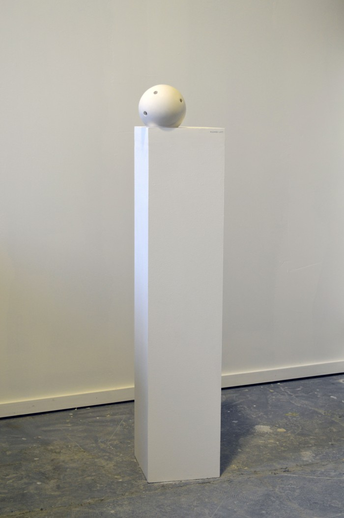A plinth stands with an off-white plaster sphere. The sphere is sitting in a small indent in the plinth and the sphere appears to have small holes in it. This is the work titled 'Hold'.