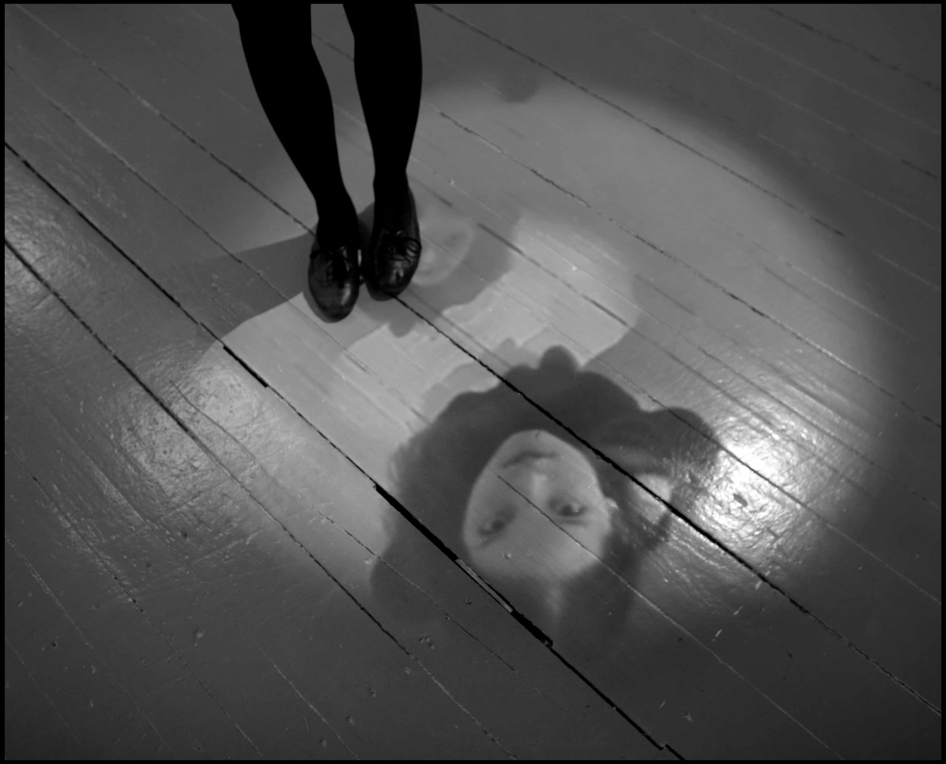 A view of the floor where we see a woman's legs and feet. On the floor a projected video shows a woman's face, which is repeated smaller and smaller.