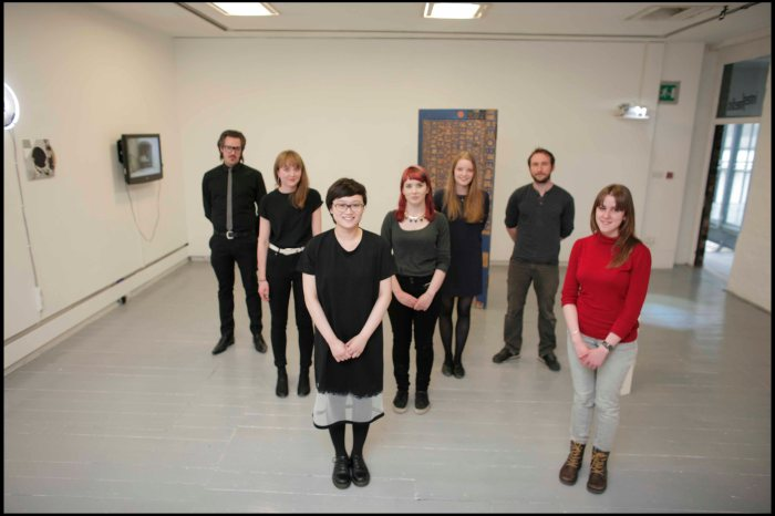 A group photo of seven artists selected for the SAY Award art commission standing inside the gallery space where there works are exhibited.