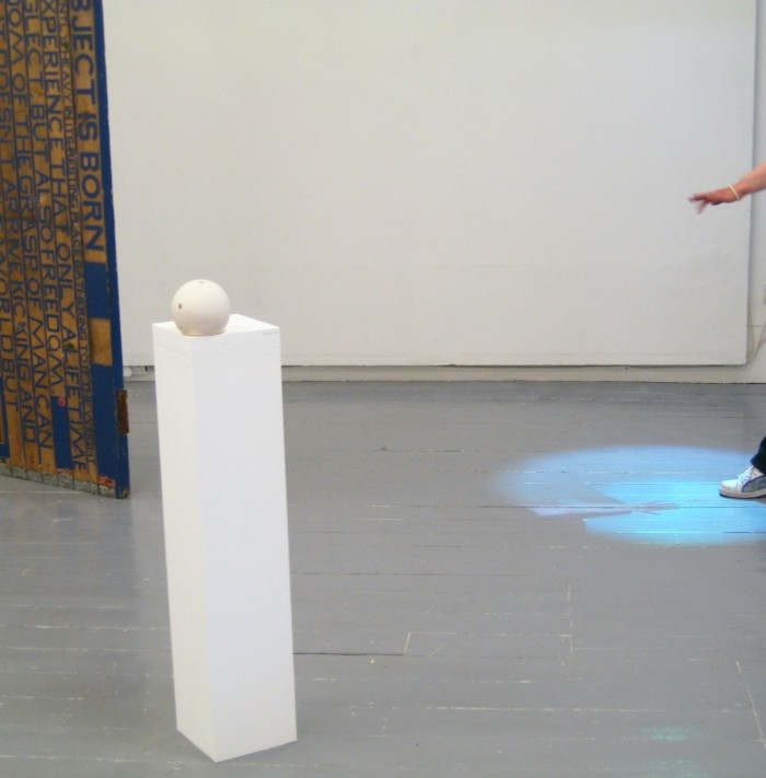 A gallery space. On the left, a plinth stands with an off-white plaster sphere. The sphere is sitting in a small indent in the plinth and the sphere appears to have small holes in it. This is the work titled 'Hold'. On the right a hand and foot reach into the frame, they are seen projected onto the floor beneath in a circular projection. That is the work titled 'Spotlight'