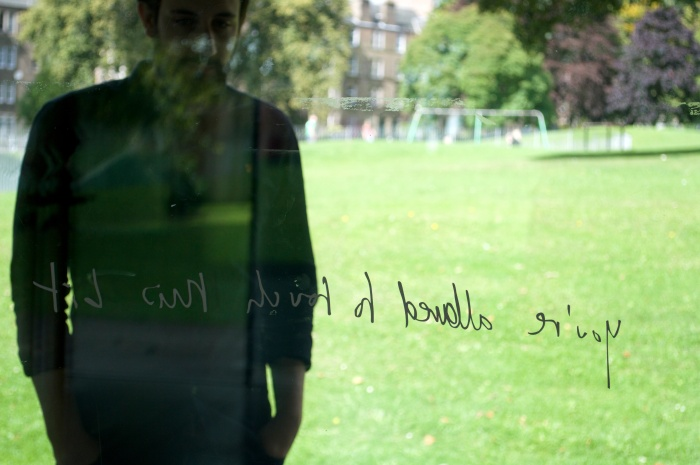 A view through a glass wall to a park. A man stands outside the glass wall, looking in. He is reading vinyl handwritten style text on the glass. From the inside, where the photo is taken from, it is more difficult to read but the text says: you're allowed to touch this bit