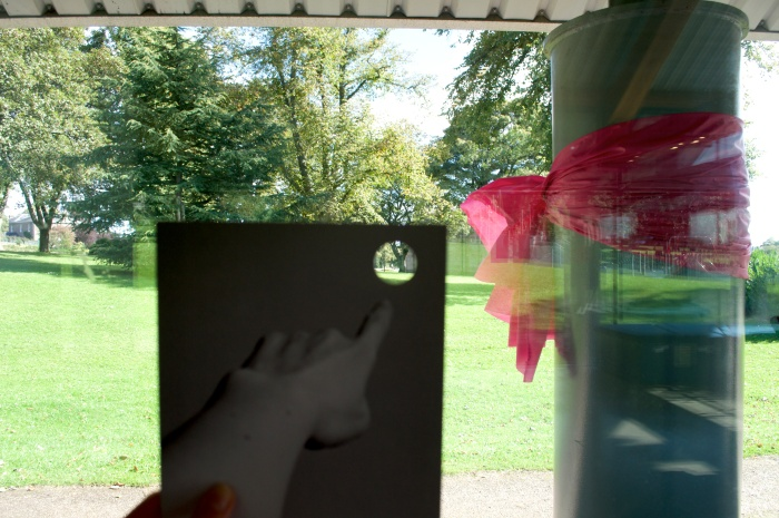 A postcard with the peephole is held up so that the peephole frames a small section of the surrounding park