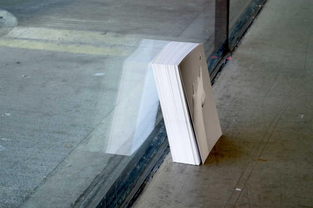 A stack of postcards rests on the floor and leans against a glass wall. The postcards are black and white and show an image of a hand reaching out and pointing.