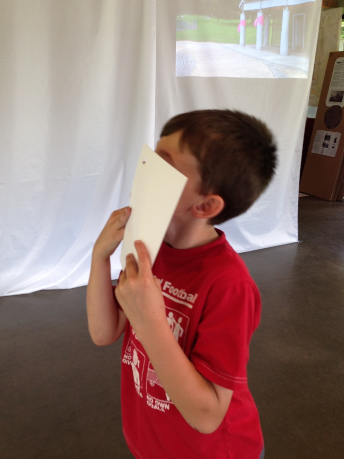 A child holds a postcard close to his face and looks through the peephole.