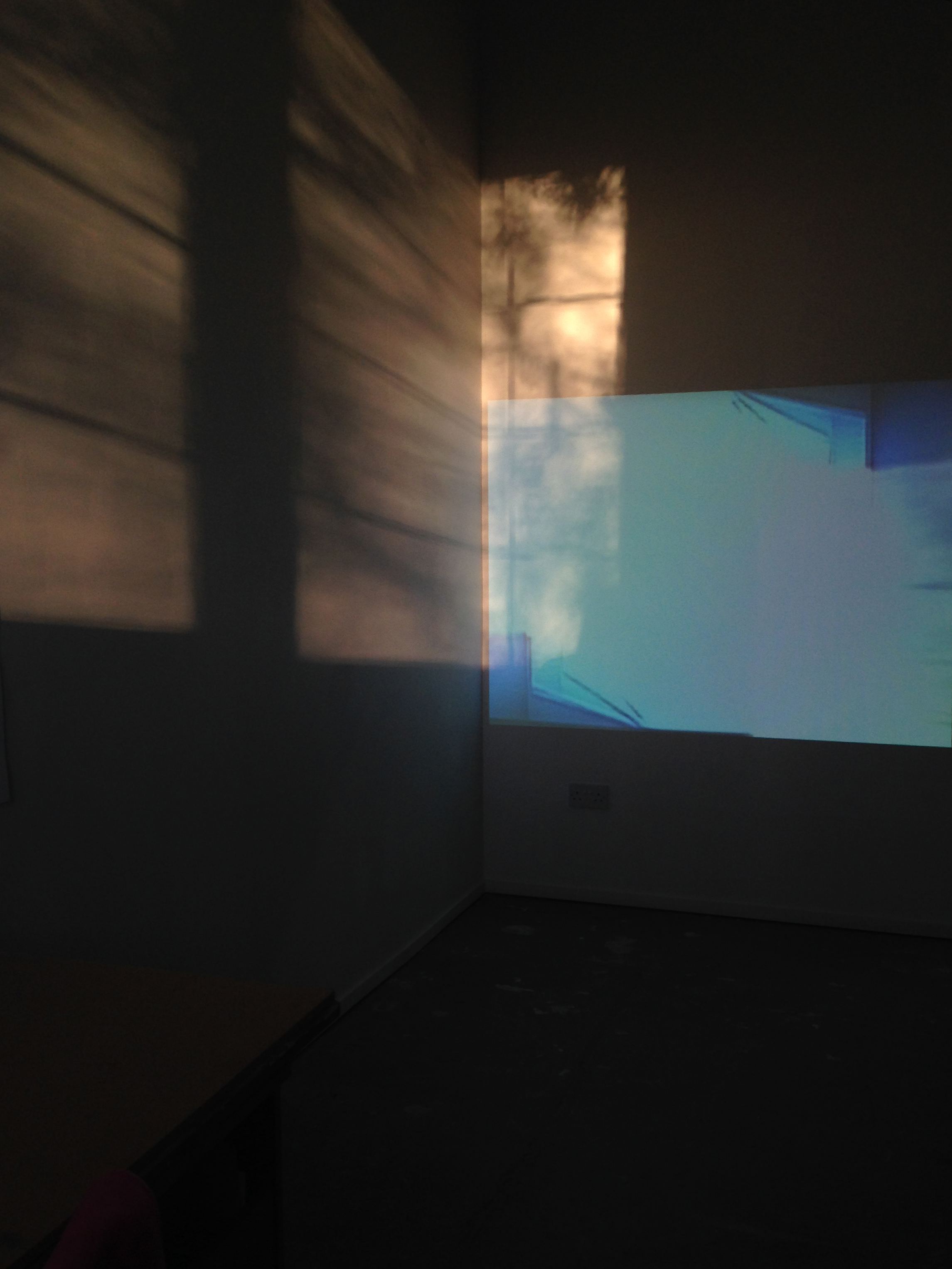 A projection on the wall is overlapped by the glow from the sun is projecting the shadow of the window frame onto the wall.