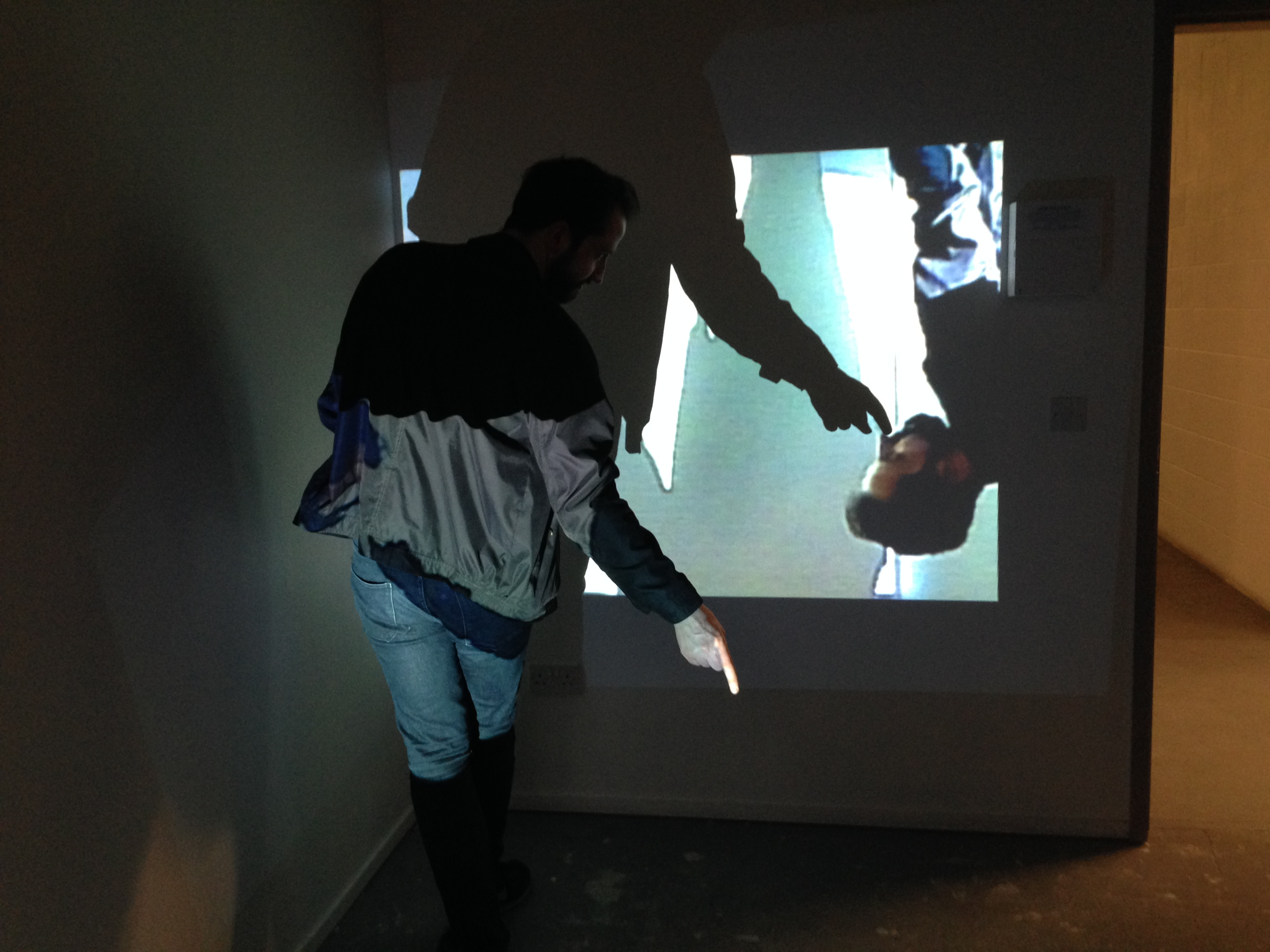 A man stands in front of a projection on a wall. His face is seen in the projection and it is repeated and getting smaller. He is holding his hand out with a pointed finger so that his shadow appears to touch his nose in the projected video.
