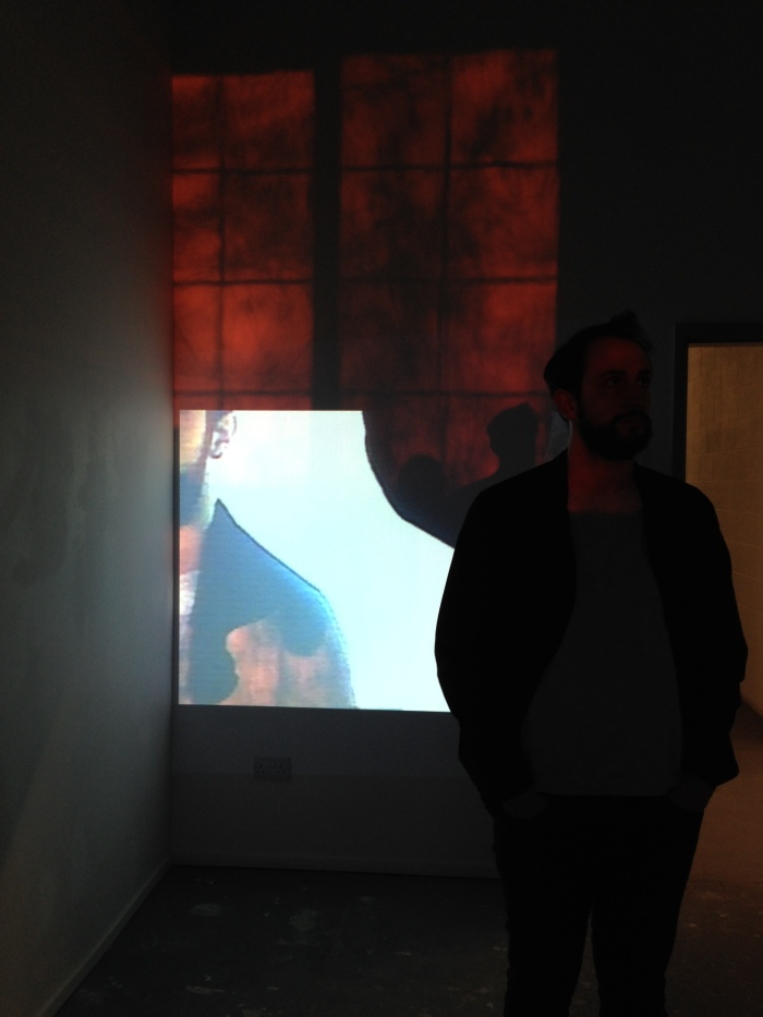 A projection on a wall shows part of a man's face and shoulder, the same man is standing nearby. Also on the wall, the red glow from sunset is projecting the shadow of the window frame onto the wall.