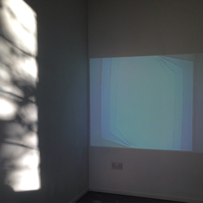 Projection on a wall which shows squares that rotate and get gradually smaller.