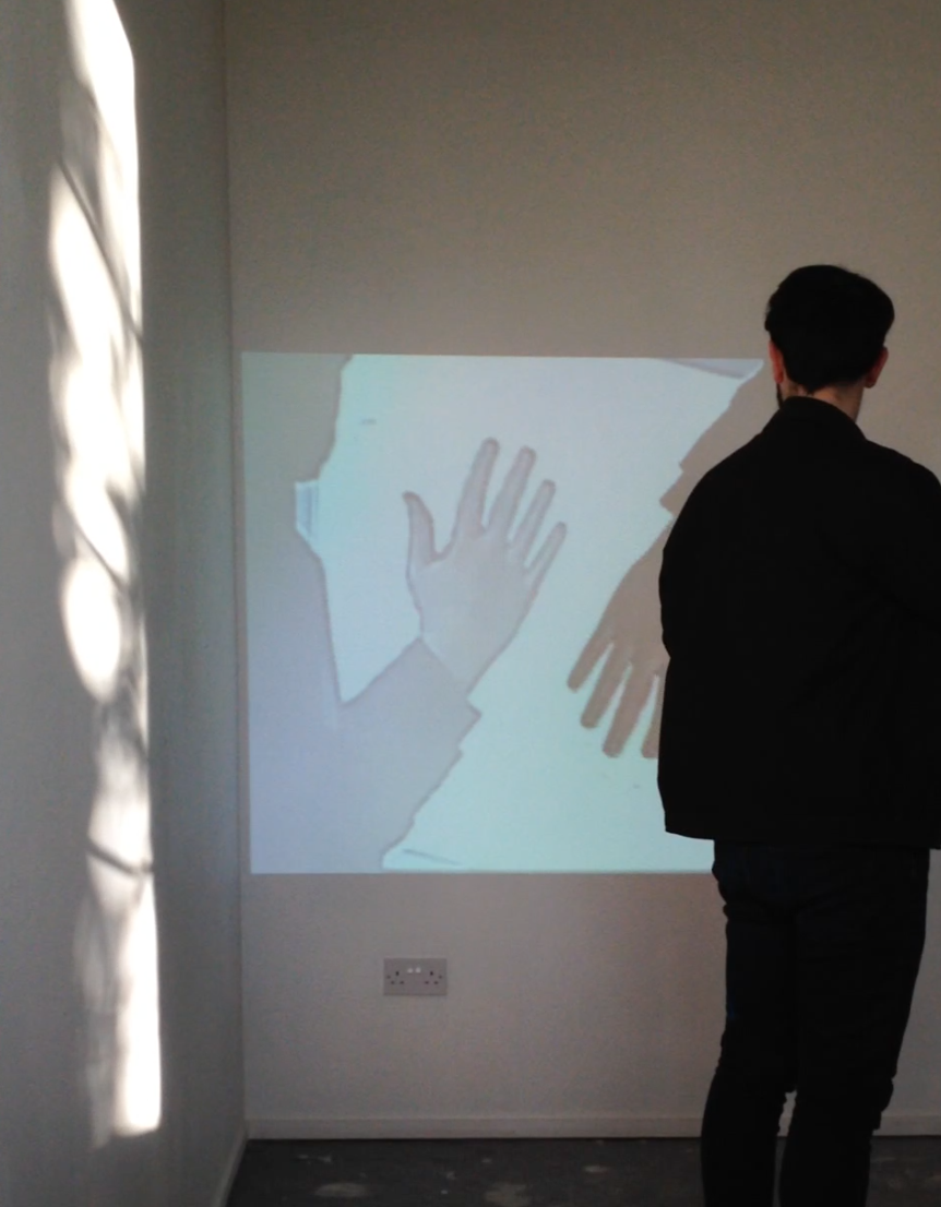 A man stands in front of a projection on a wall. His hand is seen in the projection and it is repeated and getting smaller. He waves at the screen.