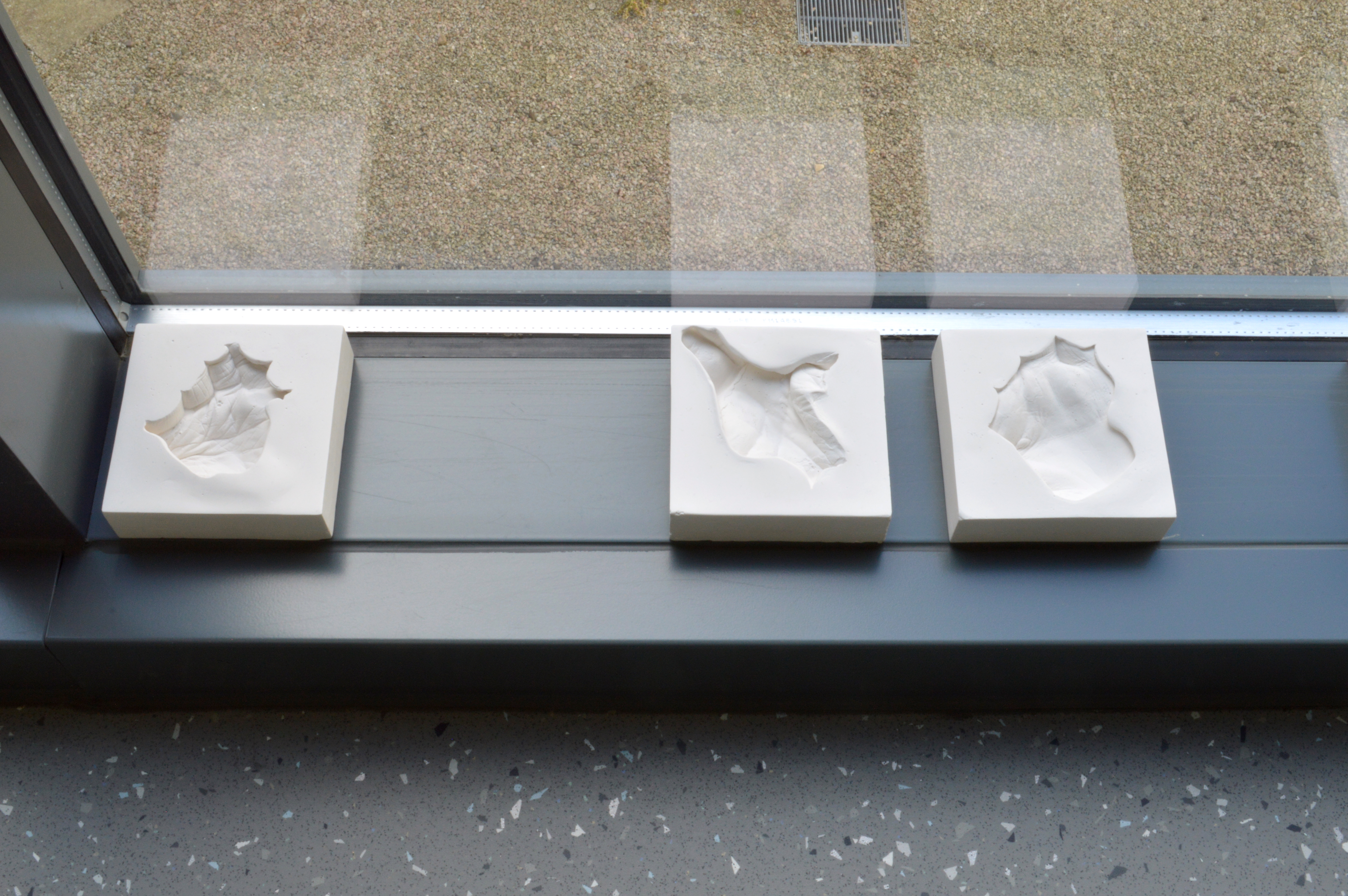 Close up of the window ledge showing three plaster blocks. Each has a unique indent of part of the palm of people's hands in it.