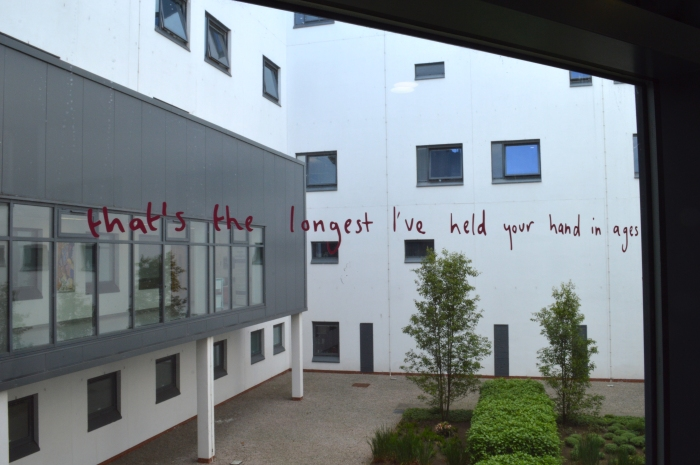 "Hospital window with pink handwritten style vinyl text. The text read ""that's the longest I've held your hand in ages'"