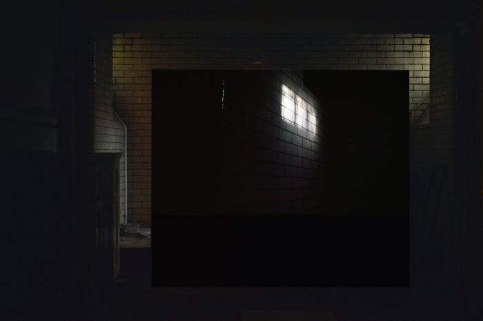 A large projection screen is positioned at the end of a white tiled basement corridor in Pollok House. Behind the screen some natural light is coming in from a window. On the screen the projection shows a section of the white tiles as they were illuminated by sunlight coming in from the window.