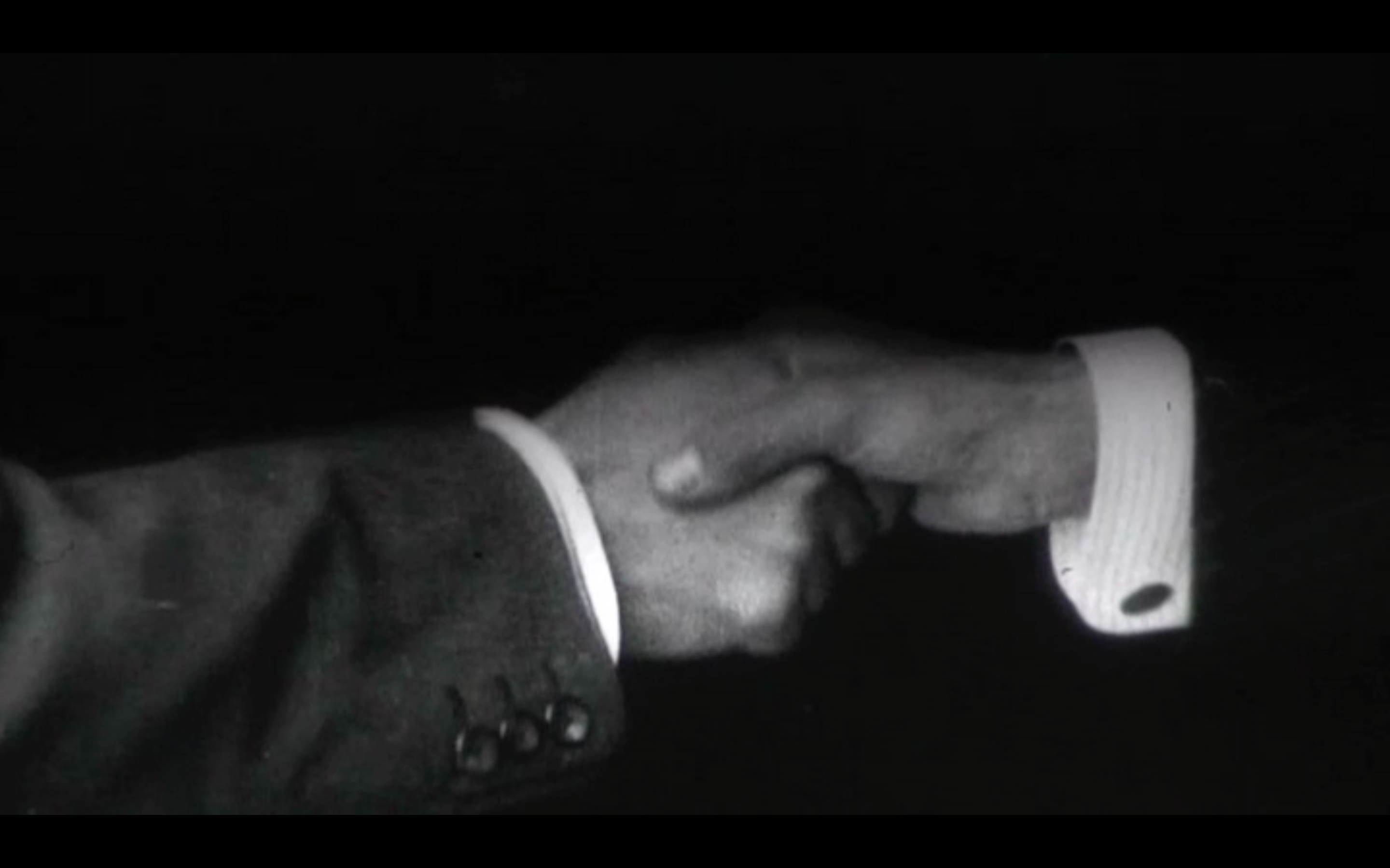 black and white archive film footage of two hands shaking. cuffs of men's clothing can be seen
