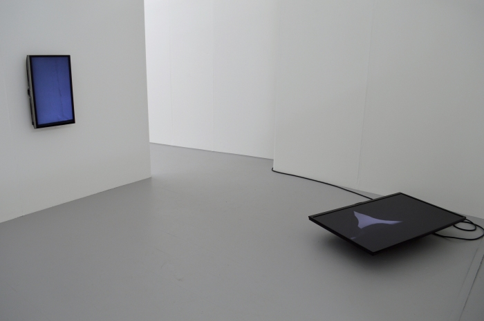 Gallery space with white walls and grey floor. At the back, there is a space which leads through to another, similar space. The left hand side has a wall-mounted TV in portrait. It's screen is blue-white. On the right hand side, towards a corner, a larger TV is sitting on the floor, facing upwards. The TV shows some black forms and grey matching the floor. The cable connecting to the power is visible coiling behind the TV.