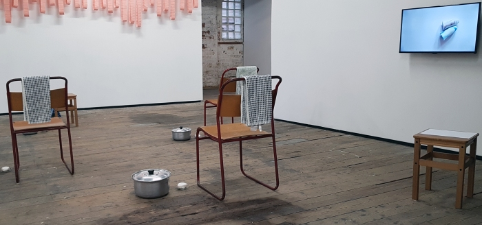 3 chairs and 2 stools sit in a cluster in the exhibition space. The chairs have basins of water, soap, and a towel beside them. The stool at the back has pages of printed text resting on it.