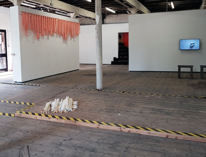 Gallery space with white walls, white pillar, and wooden floorboards with hazard tape. Sogol Mabadi's pink textile work 'Bandoleers' hang high up from a rail on one wall. In the foreground, Sogol Mabadi's work 'Knitting Needles' rests on the floor this is made of white glue sticks held together by knitting needles. These are then stacked together. A TV is mounted on a wall in the background. The screen is white-blue with two small objects on it. There are two stools in front of the TV. The video is called 'Quietly Breathing Together' and was made by Emma Helen Reid.