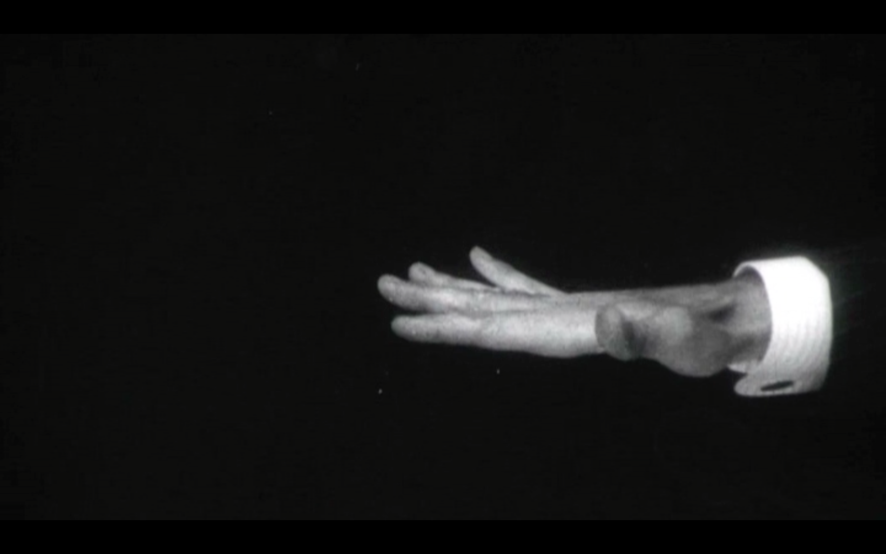 black and white archive film footage, a hand enters from the right hand side of the frame.