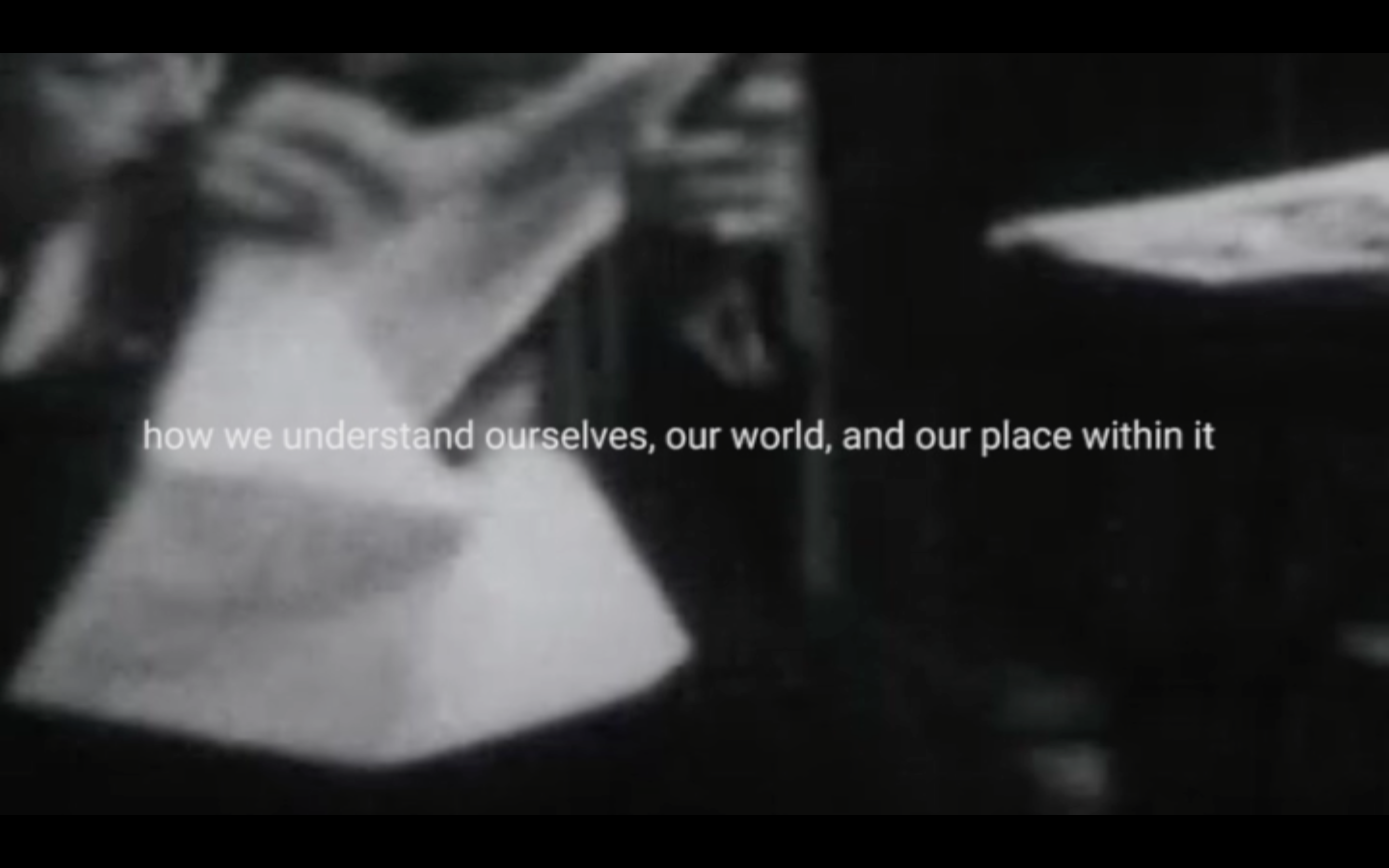 "black and white archive film footage of a hands holding a newspaper. a man's face can be seen from behind the paper. In front, text reads ""how we understand ourselves, our world, and our place within it"""