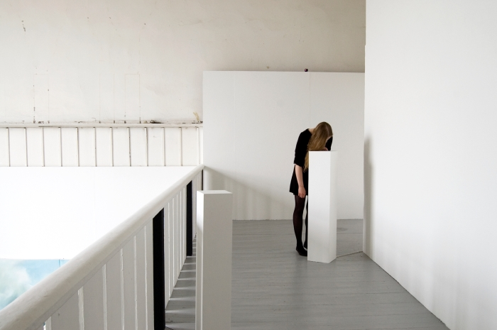 A white walled gallery space with grey floors and two white plinths can be seen. One of the plinths is taller than usual. A woman, dressed in black, is leaning over and looking into this plinth. A cable can be seen running into the bottom of the plinth.
