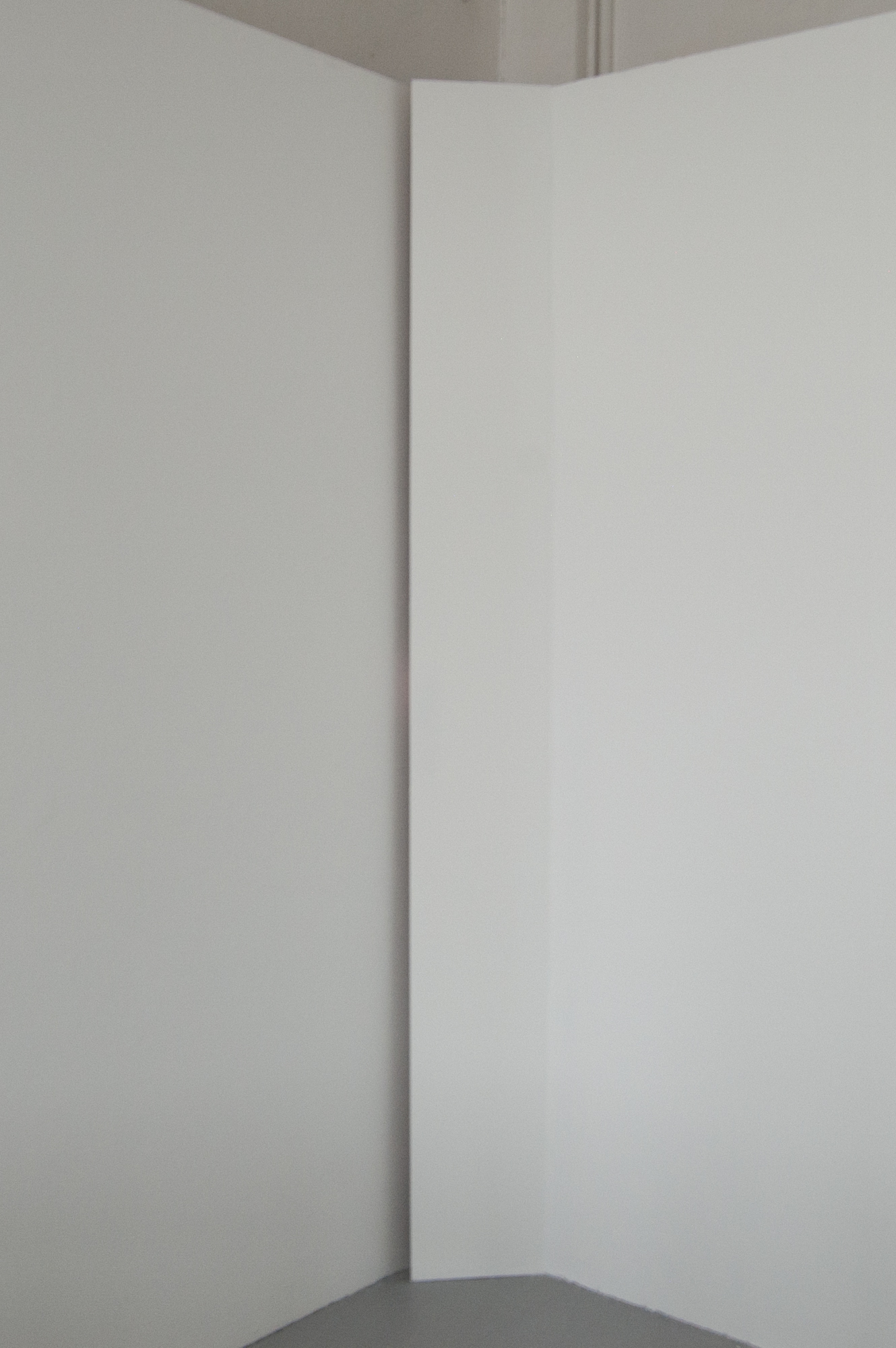 The corner of a gallery space has been partially screened off with a narrow strip of painted MDF that runs from floor to ceiling. A gap runs along the left hand edge of the screening and a feint glow of pinky-orange light can be seen reflected onto the wall.