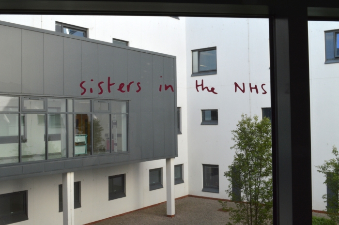 """Hospital window with pink handwritten style vinyl text. The text read """"sisters in the NHS'"""