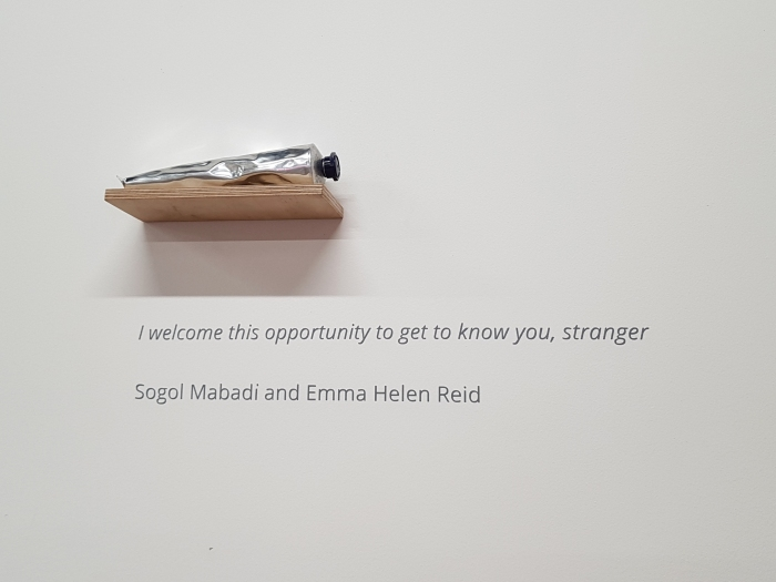 "Gallery wall - a silver tube of hand cream just fits on a small wooden shelf on the wall. Below the shelf, grey vinyl text reads ""I welcome this opportunity to get to know you, stranger"" followed by the names of the two artists ""Sogol Mabadi and Emma Helen Reid"""
