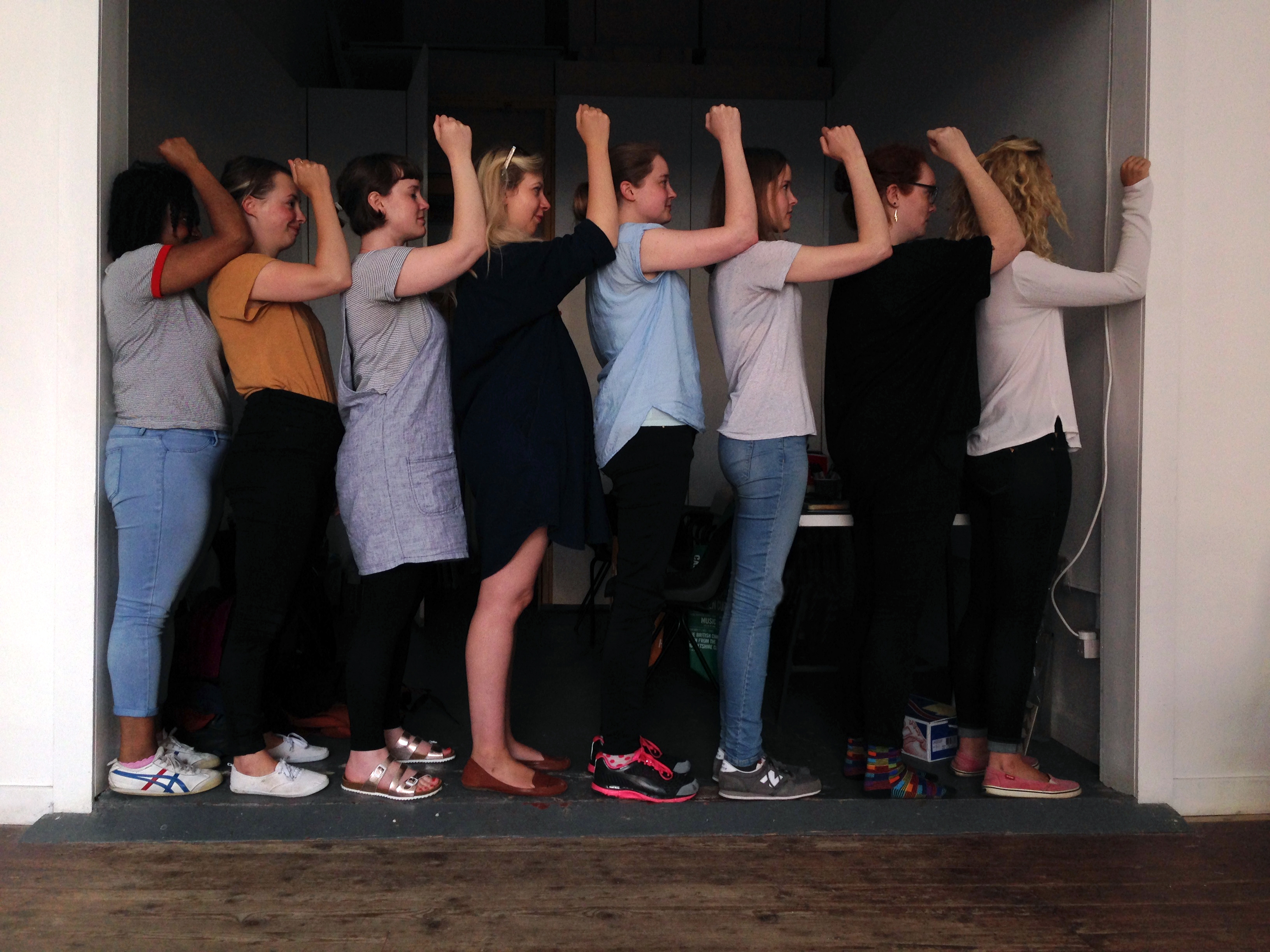eight women stand facing the right side of the frame each with their elbow on the person in front's shoulder. Together, they fill the space between two walls.