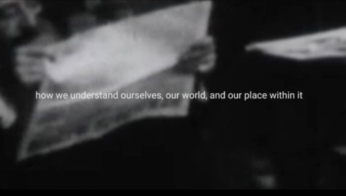 video still black and white archive video of man reading newspaper. text in middle of screen reads: how we understand ourselves, our world. and our place within it