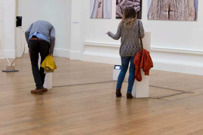 A gallery space. Two white plinths are on the floor, a couple of metres apart. A man is looking into one of them, while a woman stands beside the second, she is pointing at the man.
