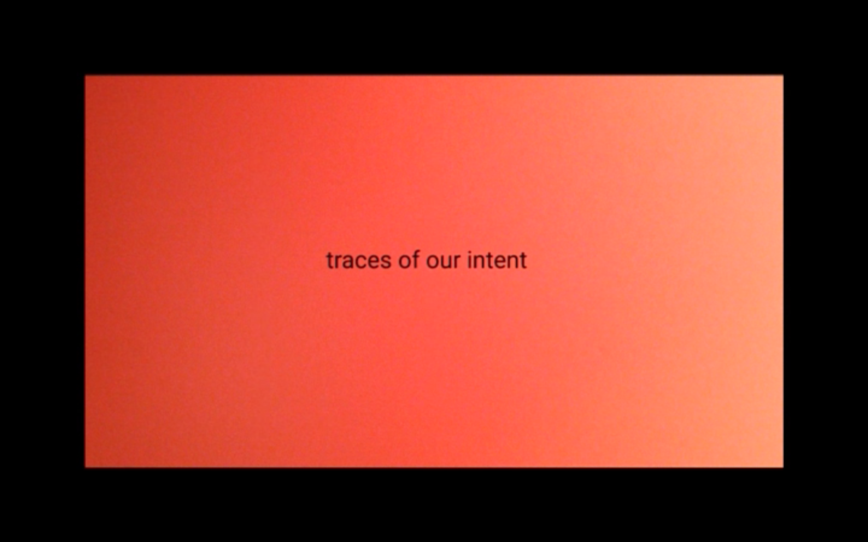 "a black border around a pinky coloured rectangle. Text in front reads ""traces of our intent"""