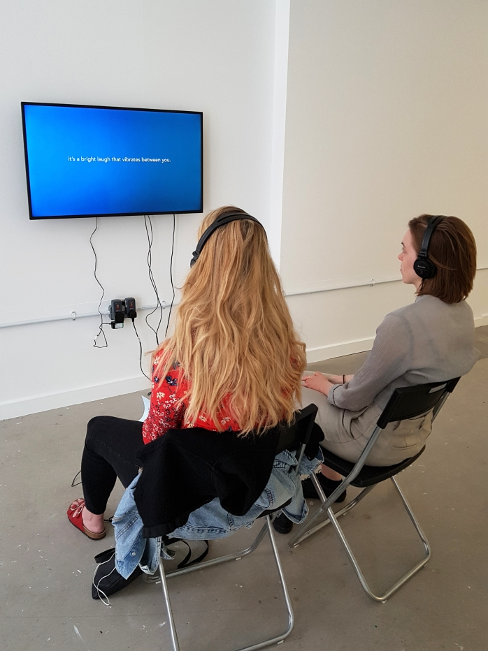 """A TV is mounted on a white gallery wall. The screen shows a bright blue background and white text in the centre saying """"it's a bright laugh that vibrates between you.""""  In front of the TV two young women sit on chairs, facing the screen, while wearing headphones."""