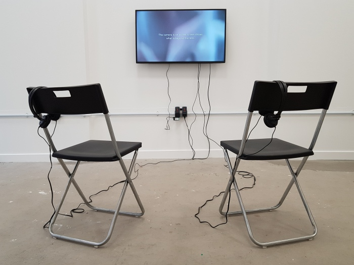 """A TV is mounted on a white gallery wall. The screen has abstract beige and white patterns with white text that says: The camera is on so the screen shows what is beyond the lens"""". In front of the TV are two chairs and headphones, the cables are trailing along the concrete floor."""