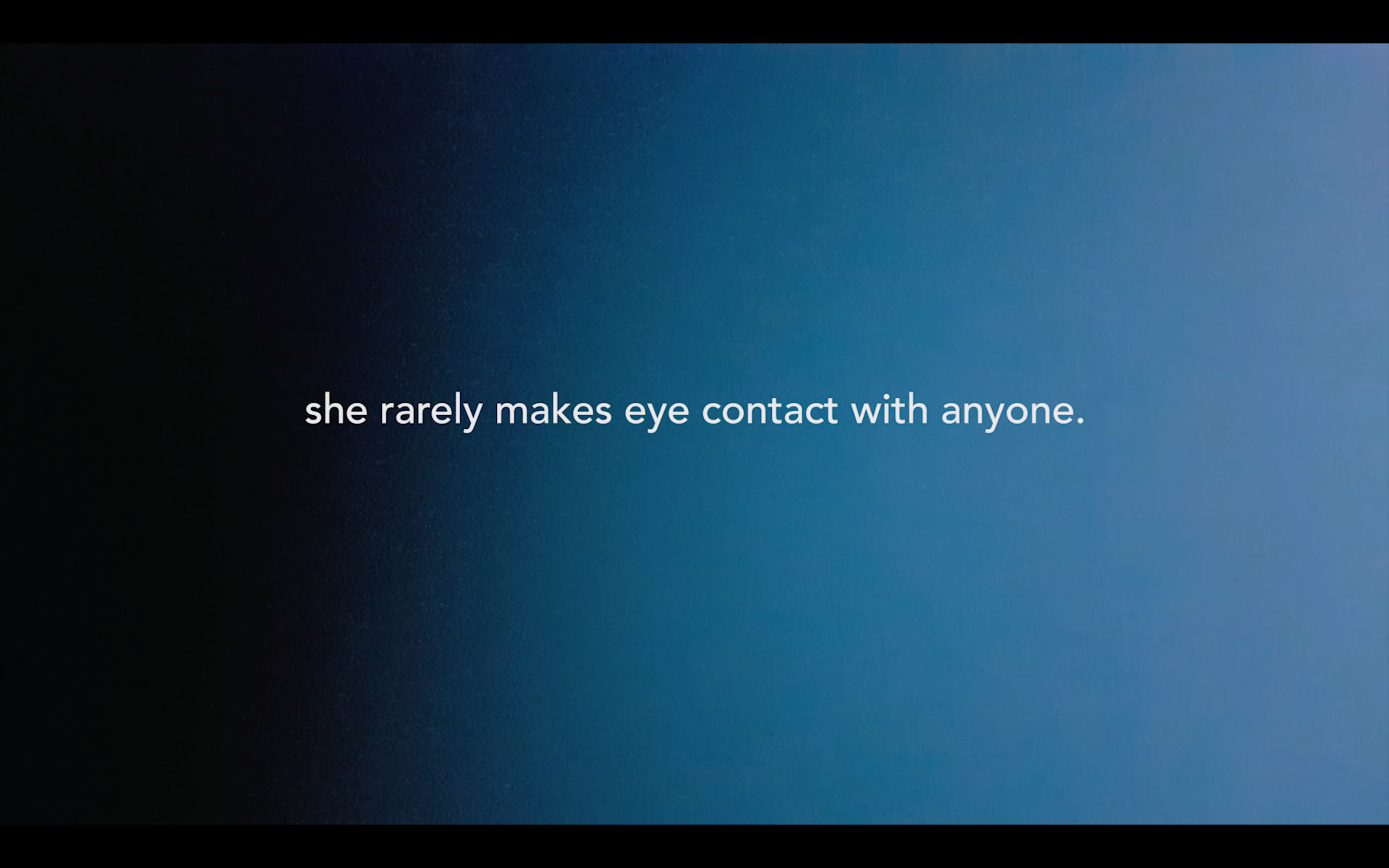"video still. Background is bright blue with a gradient and white text says ""she rarely makes eye contact with anyone"""