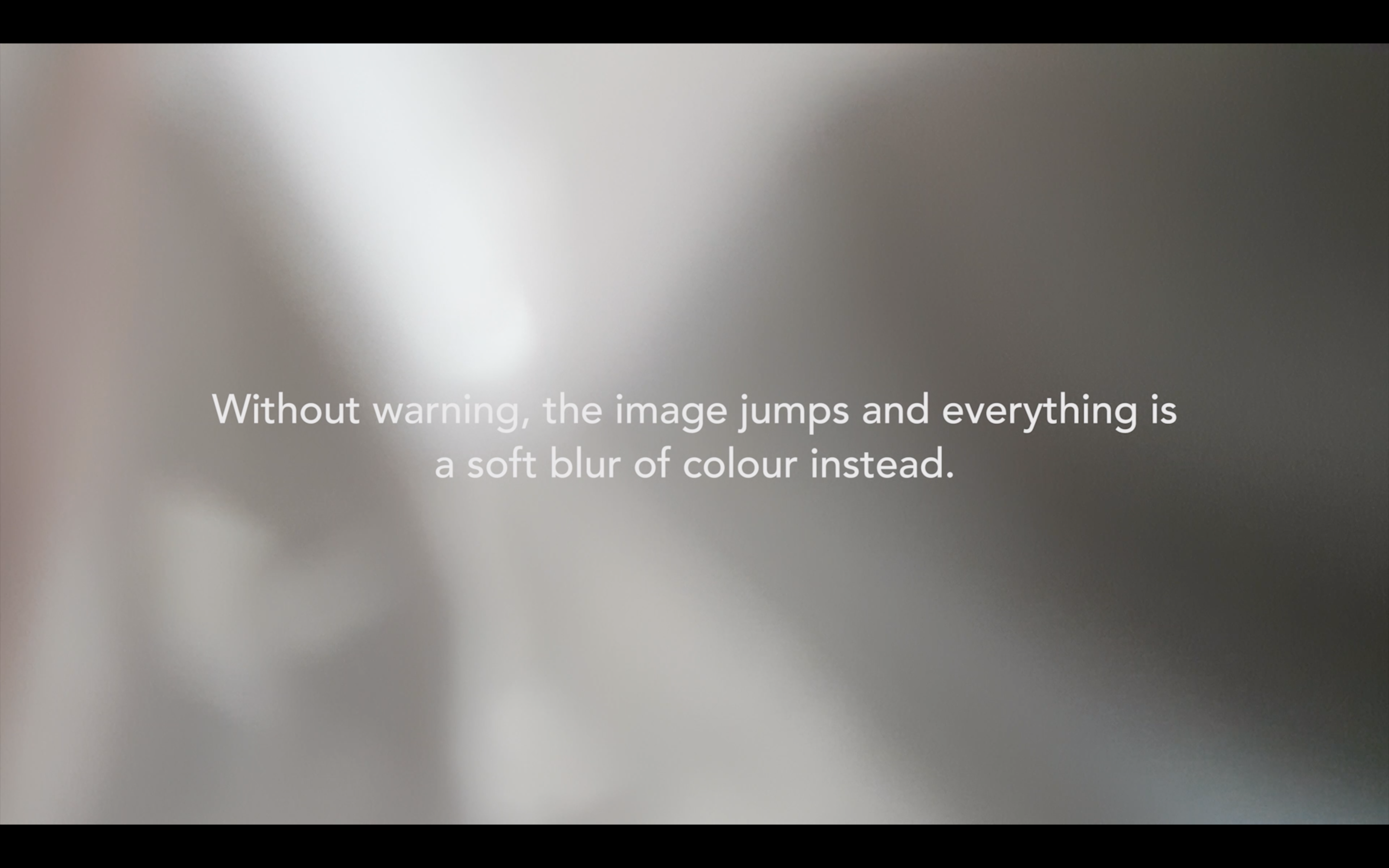 "video still. Background is abstract beige and white pattern and white text says ""Without warning the image jumps and everything is a soft blur of colour instead."""